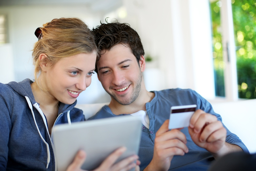 Happy young couple doing shopping on internet.jpeg