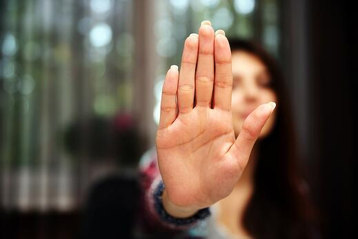 Woman with her hand extended signaling to stop (only her hand is in focus).jpeg